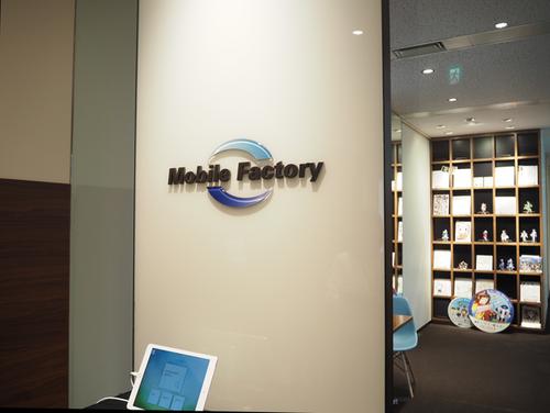 モバイルファクトリーのエントランス。奥の本棚には同社がリリース・運営するサービスのキャラクターが展示されている。